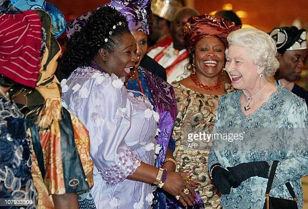 Britain's Queen Elizabeth II laughs with Noidi Okereke Onyiwke Director General of the Nigerian stock exchange during a reception for the Queen at...
