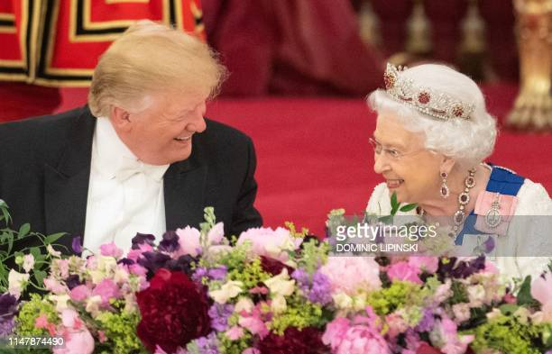 TOPSHOT Britain's Queen Elizabeth II laughs with US President Donald Trump during a State Banquet in the ballroom at Buckingham Palace in central...
