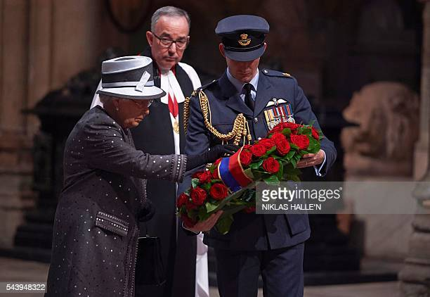Britain's Queen Elizabeth II lays a wreath made of roses and bay leaves on the Grave of the Unknown Warrior at a Service on the Eve of the Centenary...
