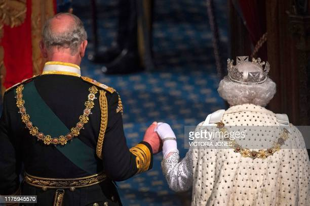 TOPSHOT Britain's Queen Elizabeth II leaves with Britain's Prince Charles Prince of Wales after delivering the Queen's Speech at the State Opening of...