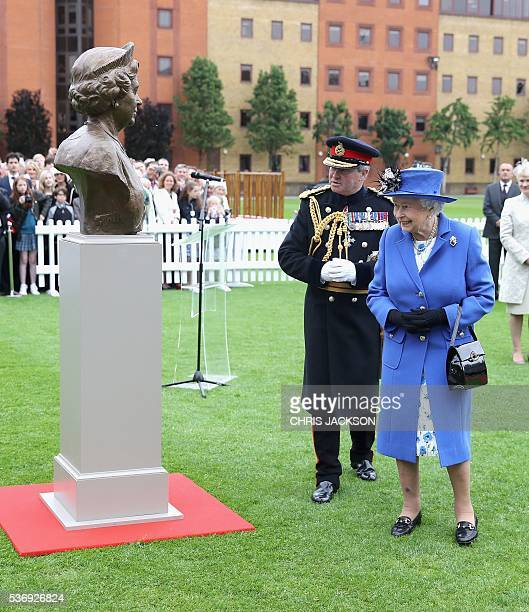 Britain's Queen Elizabeth II looks at a bronze bust of herself as she visits the Honourable Artillery Company in London on June 1 2016 The engagement...