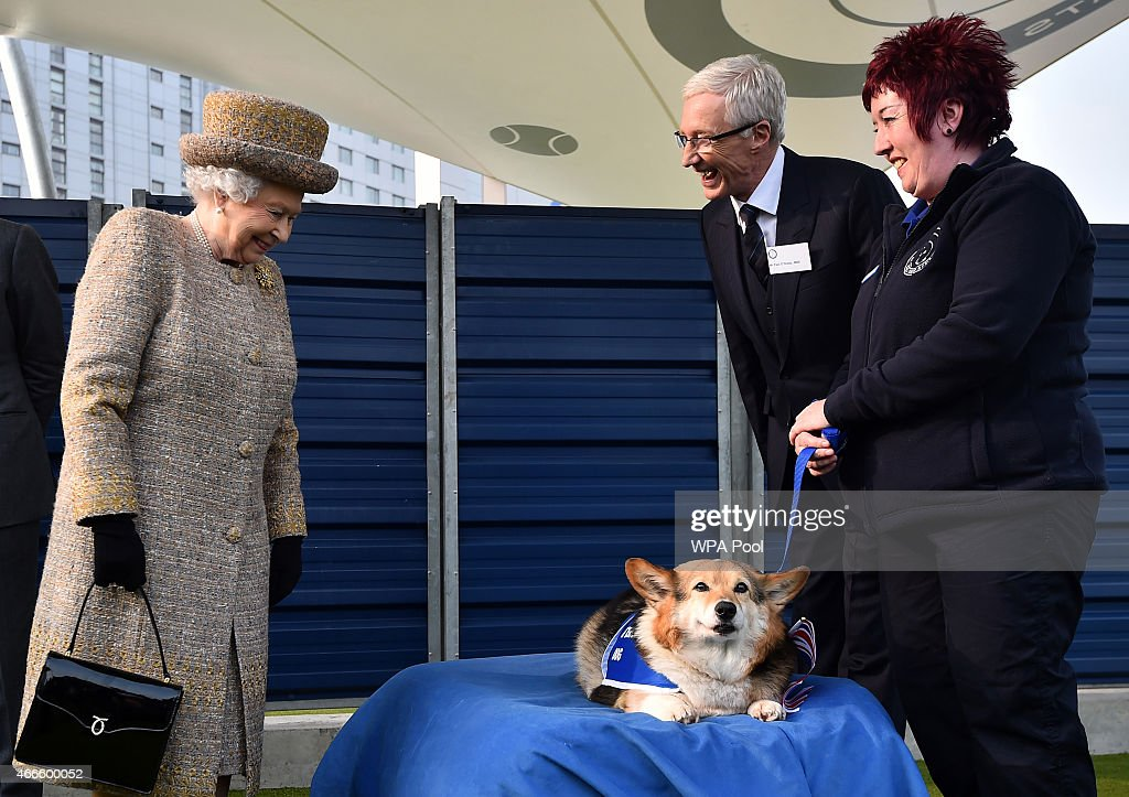 Britain's Queen Elizabeth II looks at a Corgi dog as British television presenter Paul O'Grady (2nd R) looks on during the opening of the new Mary Tealby dog kennels at Battersea Dogs and Cats Home in London on March 17, 2015.