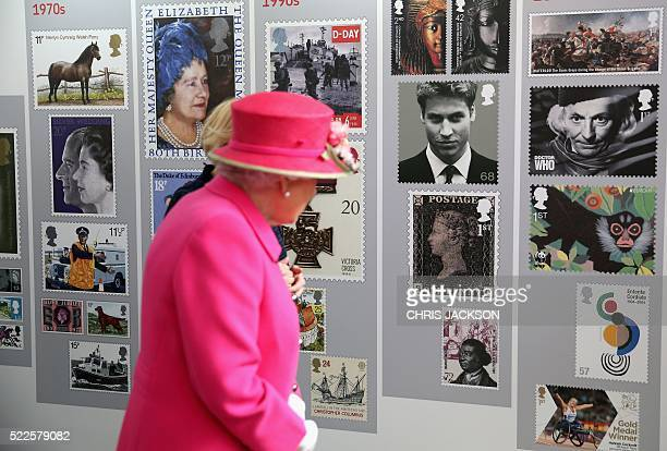 Britain's Queen Elizabeth II looks at a display of images of Royal Mail postage stamps some depicting members of the Royal Family including the Queen...