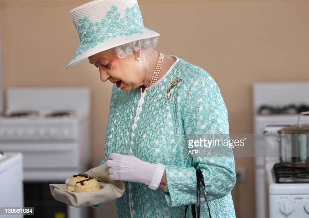 Britain's Queen Elizabeth II looks at homemade scones as she visits the kitchen at Clontarf Aboriginal College in Perth on October 27 2011 The queen...