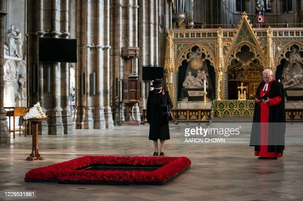 Britain's Queen Elizabeth II looks at the grave of the Unknown Warrior during a service to mark the centenary of the burial of the Unknown Warrior...