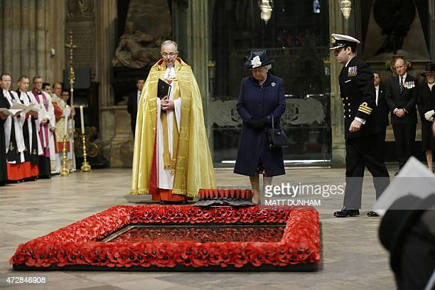 Britain's Queen Elizabeth II looks down after a wreath was laid on her behalf at the grave of the Unknown Warrior flanked by the Dean of Westminster...