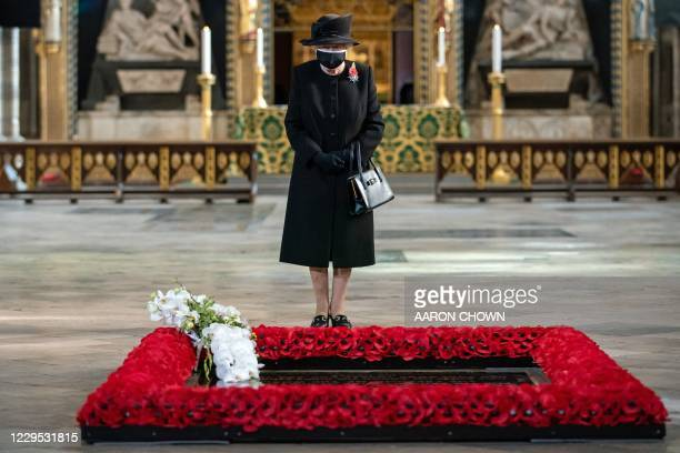 Britain's Queen Elizabeth II looks on after her Equerry, Lieutenant Colonel Nana Kofi Twumasi-Ankrah placed a bouquet of flowers at the grave of the...