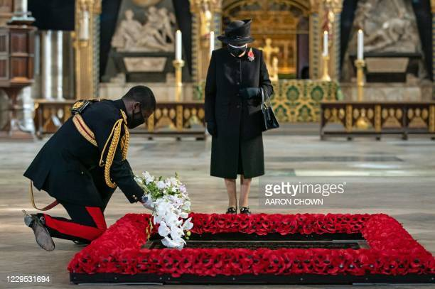 Britain's Queen Elizabeth II looks on as her Equerry, Lieutenant Colonel Nana Kofi Twumasi-Ankrah places a bouquet of flowers at the grave of the...