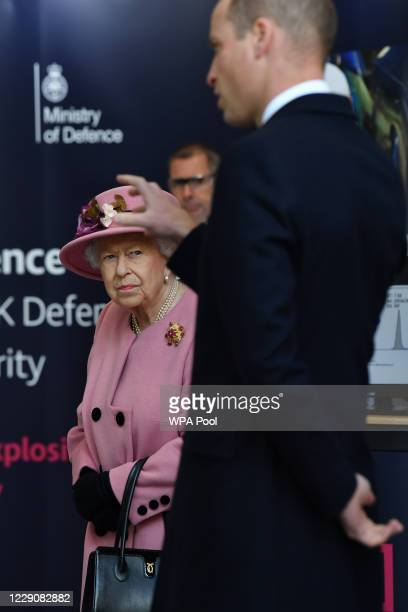 Britain's Queen Elizabeth II looks on as Prince William Duke of Cambridge asks a question about forensics work as they visit the Energetics Analysis...