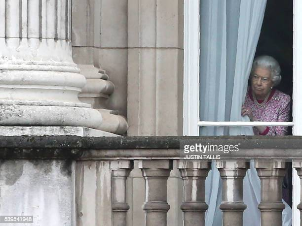 Britain's Queen Elizabeth II looks out from Buckingham Palace as guests gather for the Patron's Lunch a street party to be held along the Mall in...