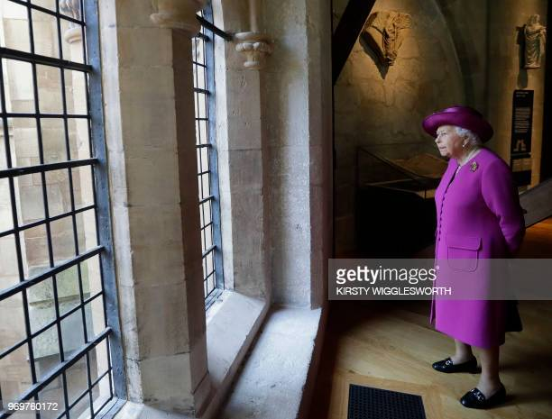 Britain's Queen Elizabeth II looks through a window as she walks through The Queen's Diamond Jubilee Galleries at Westminster Abbey in London on June...