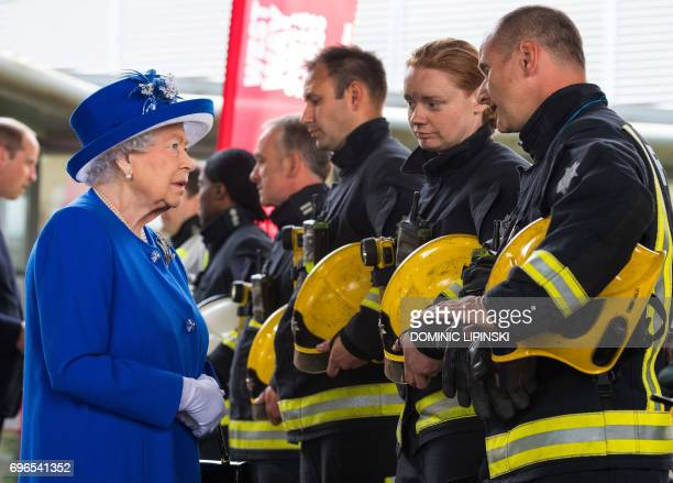 Britain's Queen Elizabeth II meets firefighters during a visit to the Westway Sports Centre which is providing temporary shelter for those who have...