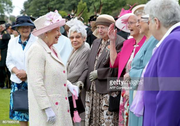 Britain's Queen Elizabeth II meets members of the Glasgow Wrens Association as she attends the annual garden party at the Palace of Holyroodhouse in...