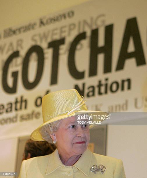 Britain's Queen Elizabeth II passes a mockup poster of British newspaper headlines as she visits the British Library in London 23 May 2006 Together...