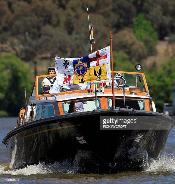 Britain's Queen Elizabeth II peers under the royal standard as she and Prince Philip cruise on a navy barge on Lake Burley Griffin during their visit...