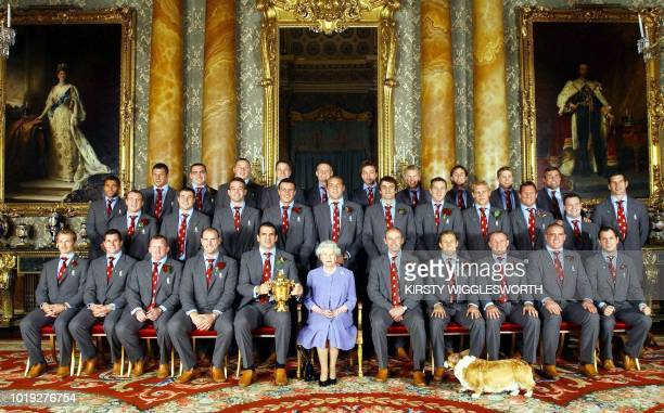 Britain's Queen Elizabeth II poses 08 December with the England rugby squad at a reception at Buckingham Palace in London to celebrate winning the...