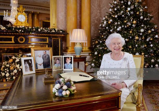 Britain's Queen Elizabeth II poses at a desk in the 1844 Room at Buckingham Palace London on December 13 2017 after recording her Christmas Day...