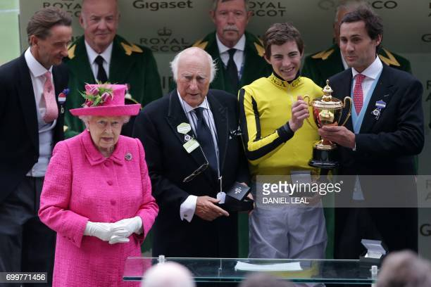 Britain's Queen Elizabeth II poses for a photograph with owner of Big Orange Bill Gredley jockey James Doyle and owner Tim Gridley after Big Orange...