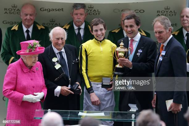 Britain's Queen Elizabeth II poses for a photograph with owner of Big Orange Bill Gredley jockey James Doyle owner Tim Gridley and trainer Michael...