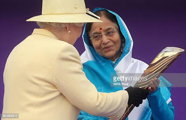 Britain's Queen Elizabeth II presents India's President Prathibha Devi Singh Patil with the baton to launch the XIX Commonwealth Games Queen's Baton...