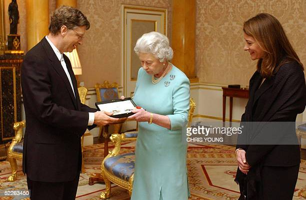Britain's Queen Elizabeth II presents Microsoft tycoon Bill Gates with his honorary knighthood at Buckingham Palace London Wednesday March 2 2005...