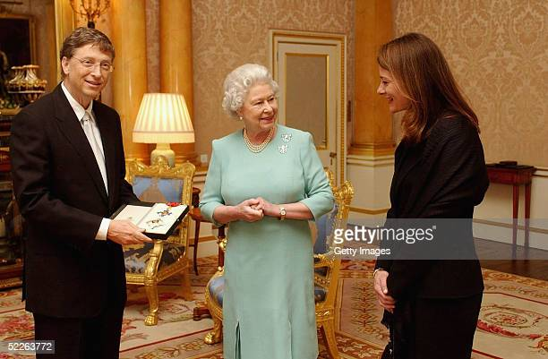 Britain's Queen Elizabeth II presents Microsoft tycoon Bill Gates with his honorary knighthood watched by his wife Melinda Gates on March 2 2005 at...