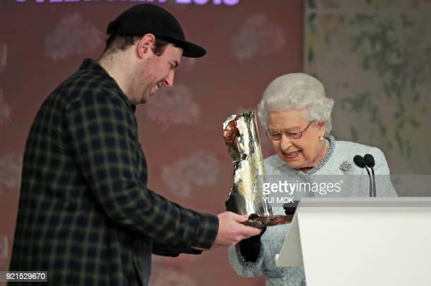 Britain's Queen Elizabeth II presents the inaugural Queen Elizabeth II Award for British Design to British fashion designer Richard Quinn during her...