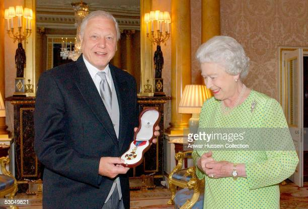 Britain's Queen Elizabeth II presents TV naturalist Sir David Attenborough with the Insignia of the Order of Merit, a personal award from the Queen...