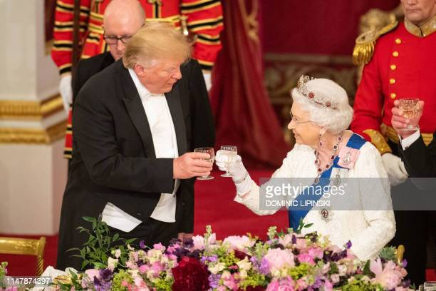 TOPSHOT Britain's Queen Elizabeth II raises a glasses with US President Donald Trump during a State Banquet in the ballroom at Buckingham Palace in...
