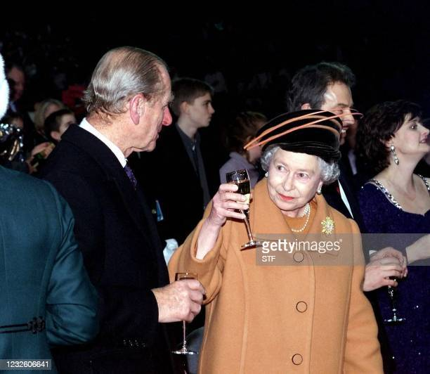 Britain's Queen Elizabeth II raises her champagne glass towards her husband the Duke of Edinburgh to toast the new Millenium shortly before midnight...