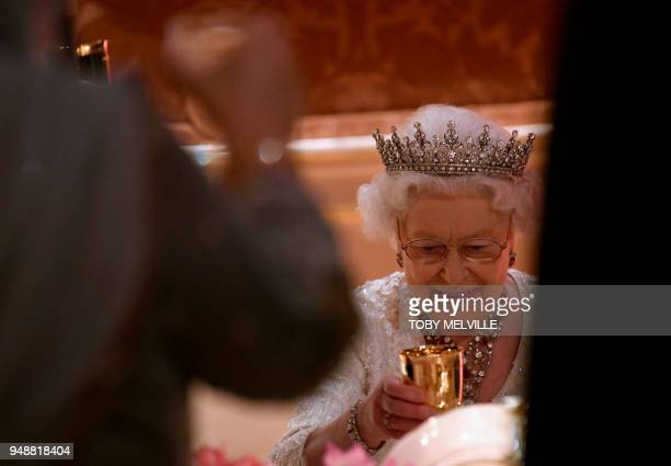 Britain's Queen Elizabeth II raises her glass during speeches in the Picture Gallery at The Queen's Dinner during The Commonwealth Heads of...