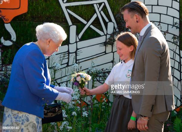 Britain's Queen Elizabeth II reacts as is present with a posy of flowers by Caitlyn James from Swansea at the Chelsea Flower Show in London on May 22...