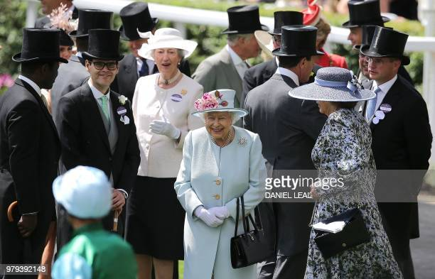 Britain's Queen Elizabeth II reacts as jockeys and horses parade in the ring on the second day of the Royal Ascot horse racing meet in Ascot west of...