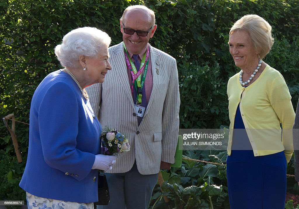 Britain's Queen Elizabeth II (L) reacts as she greets British chef and television presenter Mary Berry (R) as she visits the BBC Radio 2 Feel Good Gardens at the Chelsea Flower Show in London on May 22, 2017. The Chelsea flower show, held annually in the grounds of the Royal Hospital Chelsea, opens to the public this year from May 22. /