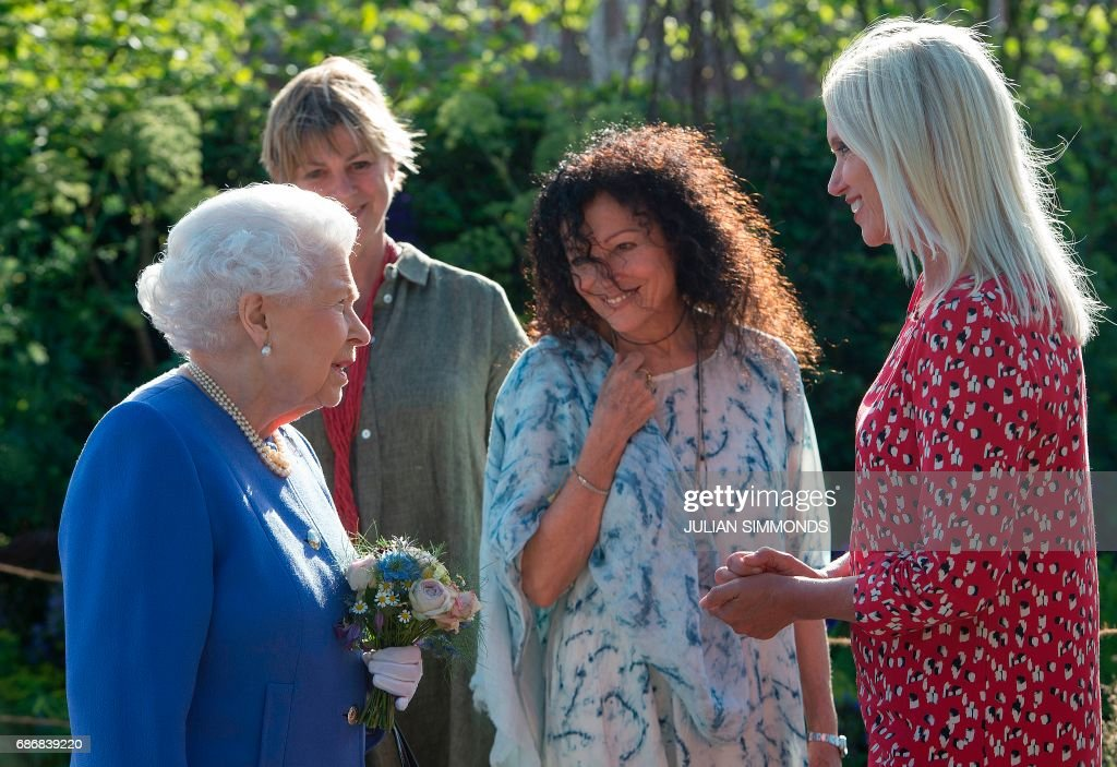 Britain's Queen Elizabeth II (L) reacts as she meets British radio and televsion presenter Anneka Rice (R) at the Chelsea Flower Show in London on May 22, 2017. The Chelsea flower show, held annually in the grounds of the Royal Hospital Chelsea, opens to the public this year from May 22. /