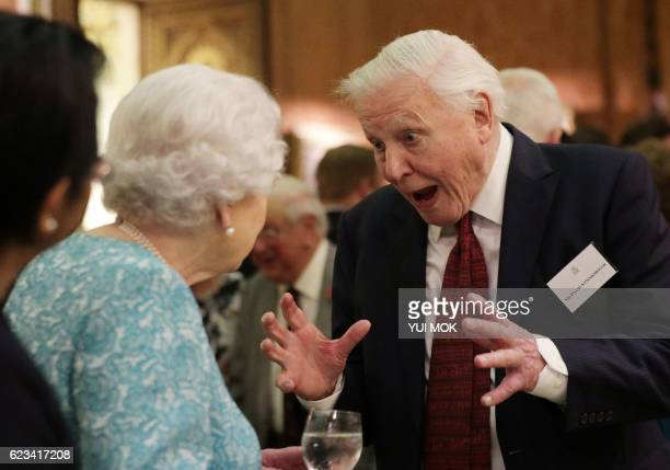 Britain's Queen Elizabeth II reacts as she talks with television presenter David Attenborough during an event at Buckingham Palace in central London...