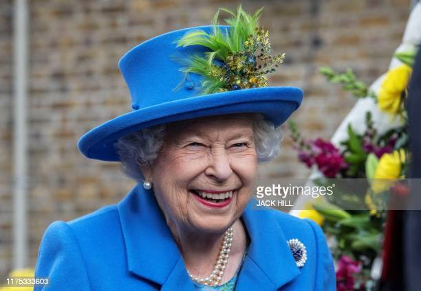 TOPSHOT Britain's Queen Elizabeth II reacts as she visits the Haig Housing Trust in Morden southwest London on October 11 to open their new veteran...