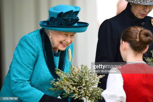 Britain's Queen Elizabeth II receives a bouquet on her arrival at the annual Braemar Gathering in Braemar central Scotland on September 1 2018 The...
