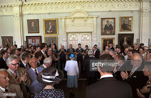 Britain's Queen Elizabeth II receives applause from MCC members inside the Long Room of the Pavilion before the start of play on the first day of the...