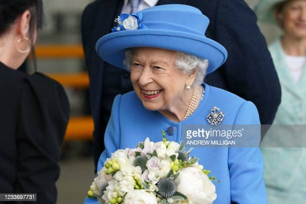 Britain's Queen Elizabeth II receives flowers as she meets employees during a visit to AG Barr's factory in Cumbernauld, east of Glasgow, where the...