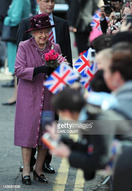 Britain's Queen Elizabeth II receives flowers from members of the public as she walks through Windsor west of London on April 30 as she makes a visit...