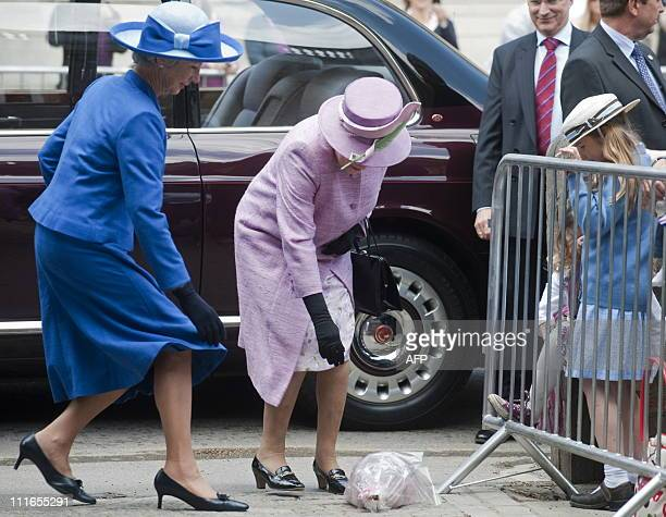 Britain's Queen Elizabeth II recieves a bouquet of flowers as she arrives to visit Eton College for the150th anniversary of the college's Combined...