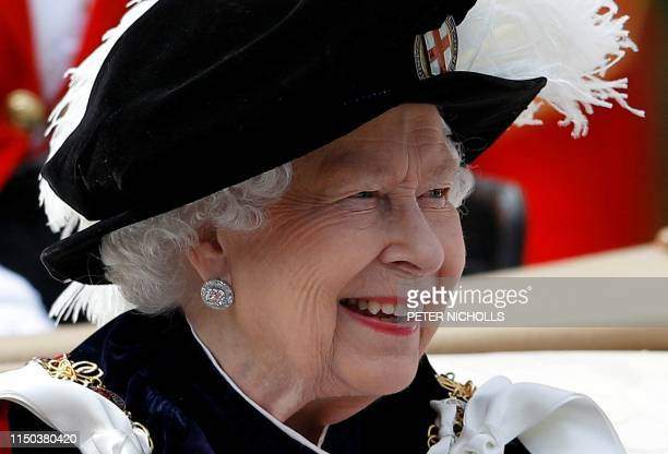 TOPSHOT Britain's Queen Elizabeth II rides in a carriage as she leaves following the Order of the Garter Service at St George's Chapel in Windsor...