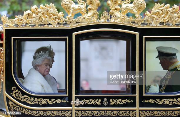 Britain's Queen Elizabeth II rides with her son Britain's Prince Charles Prince of Wales and his wife Britain's Camilla Duchess of Cornwall in the...