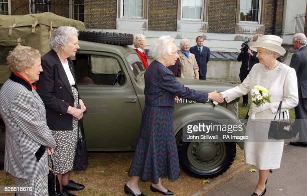 Britain's Queen Elizabeth II shakes hands with Betty Royle from London as Pat Blake from Surrey and Patsie Young from Dorset look on at the Imperial...
