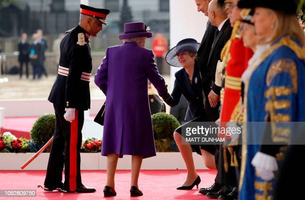 Britain's Queen Elizabeth II shakes hands with Britain's Prime Minister Theresa May on the dias as they take their places for a ceremonial welcome...