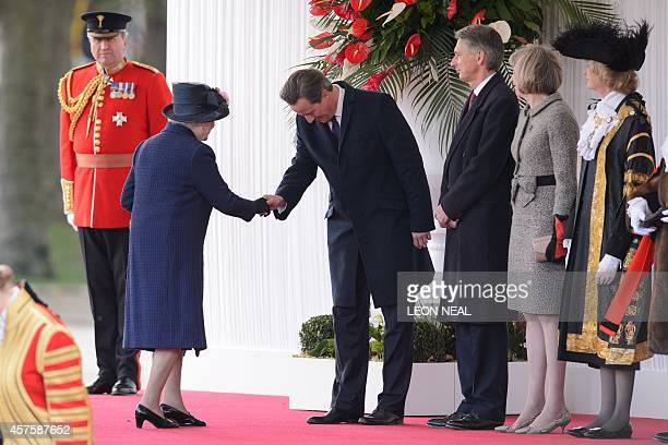 Britain's Queen Elizabeth II shakes hands with British Prime Minister David Cameron as Foreign Secretary Philip Hammond and Home Secretary Theresa...