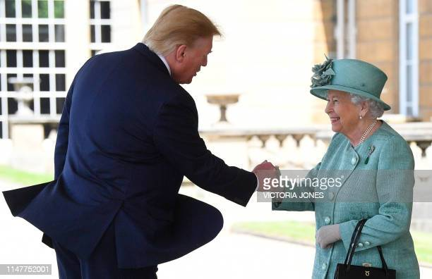 Britain's Queen Elizabeth II shakes hands with US President Donald Trump during a welcome ceremony at Buckingham Palace in central London on June 3...