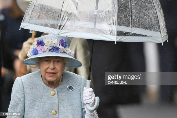 Britain's Queen Elizabeth II shelters from the rain under an umbrella as she arrives on day two of the Royal Ascot horse racing meet, in Ascot, west...