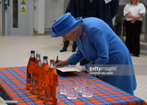 Britain's Queen Elizabeth II signs a book during a visit to AG Barr's factory in Cumbernauld, east of Glasgow, where the Irn-Bru drink is...